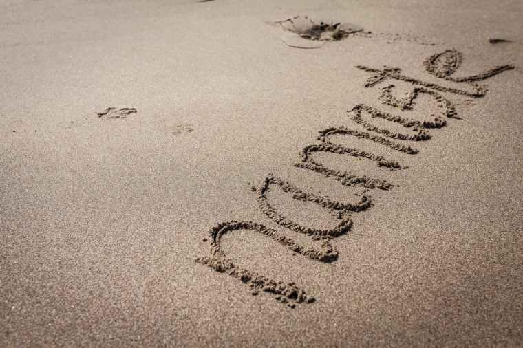 namaste text on sand